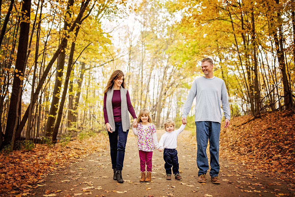 Family walking among fallen leaves on a path in autumn